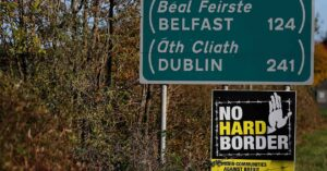 """Road sign indicating Belfast and Dublin with a """"no hard border"""" protestor sign under"""