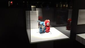 Two stuffed toys on display inside a glass enclosure. One red, the other blue.
