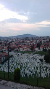 A picture of the city taken from a hilltop. In the foreground, a crematorium with many white gravestones.